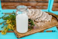 Leite caseiro e pão estaladiço saboroso no fundo de madeira da tabela Fotografia de Stock