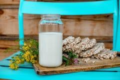 Leite caseiro e pão estaladiço saboroso no fundo de madeira da tabela Foto de Stock