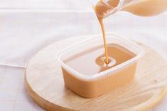 leite condensado abrandado no fundo de madeira imagem de stock