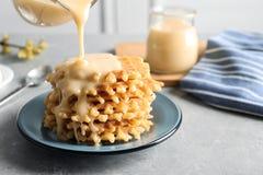 Leite condensado de derramamento do jarro em waffles no cinza, espaço para o texto Produtos láteos foto de stock