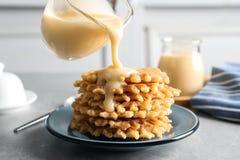 Leite condensado de derramamento do jarro em waffles no cinza Produtos láteos imagem de stock