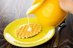 Leite condensado de derramamento do jarro na cookie nos pires, colher de chá na tabela de madeira imagem de stock royalty free
