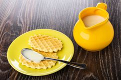 Leite condensado na colher na cookie nos pires amarelos, jarro com leite condensado na tabela de madeira fotos de stock royalty free