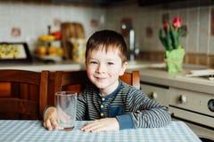 Leite da bebida do rapaz pequeno na cozinha na manhã Ele que guarda um vidro vazio Foto de Stock