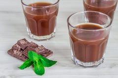Leite de chocolate em um vidro em uma superfície de madeira Imagens de Stock Royalty Free