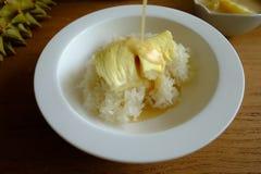 Leite de coco de derramamento na cobertura do arroz pegajoso com o durian na tabela de madeira fotografia de stock royalty free