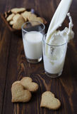 Leite de derramamento com as cookies na forma de um coração Fotos de Stock Royalty Free
