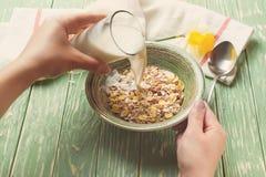 Leite de derramamento da mulher saudável do café da manhã na bacia com muesli toned fotografia de stock royalty free