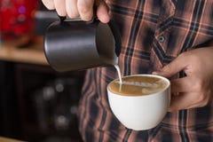 Leite de derramamento de Barista no café do capuccino Imagem de Stock