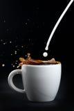 Leite de derramamento no café Fotografia de Stock