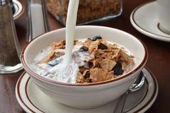 Leite de derramamento no cereal do farelo Foto de Stock Royalty Free
