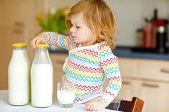 Leite de vaca bebendo da menina adorável da criança para a filha bonito do bebê do café da manhã com lotes das garrafas Criança s fotos de stock