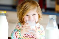 Leite de vaca bebendo da menina adorável da criança para a filha bonito do bebê do café da manhã com lotes das garrafas Criança s foto de stock