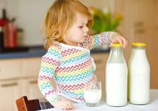 Leite de vaca bebendo da menina ador?vel da crian?a para a filha bonito do beb? do caf? da manh? com lotes das garrafas Crian?a s imagens de stock royalty free