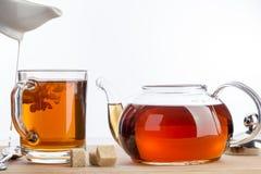 Leite derramado para o copo do chá Foto de Stock Royalty Free