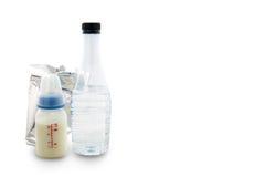 Leite do bebê na garrafa, no pacote do leite de pó, e na água para o bebê, sobre Fotografia de Stock