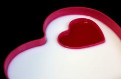 Leite e atolamento na placa dada forma coração Foto de Stock