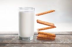 Leite e biscoitos que flutuam na tabela de madeira Imagens de Stock Royalty Free