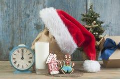 Leite e cookies para o chapéu de Santa Claus e de Santa sobre o CCB de madeira foto de stock royalty free