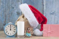 Leite e cookies para o chapéu de Santa Claus e de Santa sobre o CCB de madeira foto de stock