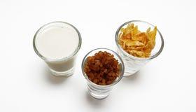 Leite, flocos de milho e açúcar mascavado de soja no fundo branco Fotos de Stock