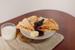 Leite fresco e panquecas quentes na tabela com manteiga e doce ru Imagem de Stock Royalty Free