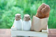 Leite nas garrafas de vidro e no pão em um saco de kraft em uma caixa de madeira contra imagens de stock