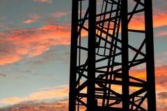 Leiter auf industriellem Kran bei Sonnenuntergang lizenzfreie stockfotos