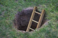 Leiter, die aus ein Loch im Boden herauskommt Lizenzfreies Stockbild