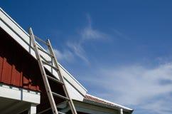 Leiter an einem mit Ziegeln gedeckten Dach Stockbild