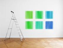 Leiter im leeren Raum, weiße Wand mit farbigen Farbenproben Lizenzfreie Stockfotos