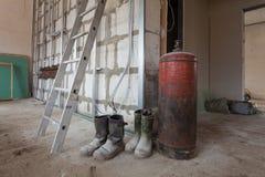 Leiter-, staubige und schmutzigegummistiefel von Arbeitskräften und von großem Gaskessel in der Wohnung während während auf der U Stockfotos
