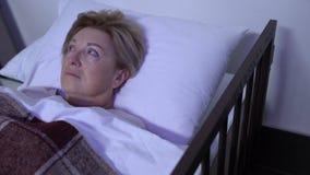 Leito do enfermo de encontro comprimido da mulher superior doente na frente da tevê, pensando sobre a doença filme