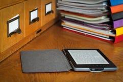 Leitor de Ebook na biblioteca Imagem de Stock Royalty Free