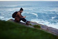 Leitura à moda do indivíduo do moderno na mensagem de telefone da pilha do amigo ao sentar-se em uma rocha perto do mar Fotografia de Stock Royalty Free