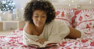 Leitura africana bonita calma da mulher na cama imagem de stock