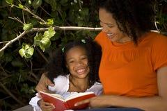 Leitura afro-americano loving da mãe com sua filha imagens de stock