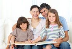 Leitura alegre da família junto no sofá Fotografia de Stock