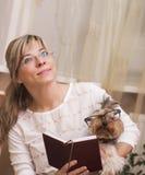 Leitura alegre da mulher com o yorkshire terrier Foto de Stock Royalty Free
