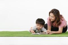 Leitura asiática da criança com mãe fotografia de stock