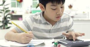 Leitura asiática da criança que calcula e que escreve para fazer em casa trabalhos de casa filme
