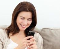 Leitura atrativa da mulher sms em seu telemóvel Foto de Stock