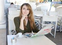 Leitura bonita da jovem mulher no café foto de stock royalty free