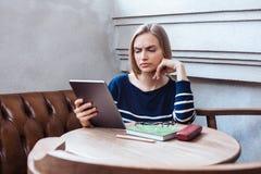 A leitura bonita da menina com uma tabuleta e não é satisfeita com o que viu Mulher que estuda e que relaxa estando em um café Foto de Stock Royalty Free