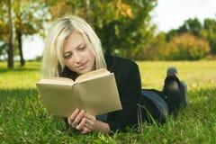 Leitura bonita da menina no parque Fotos de Stock
