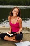 Leitura bonita da menina por um lago imagens de stock royalty free