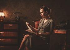 Leitura bonita da mulher no interior retro foto de stock royalty free