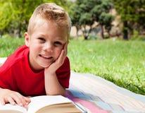 Leitura bonito do rapaz pequeno em um piquenique Imagens de Stock Royalty Free