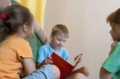 A leitura caçoa em casa Fotos de Stock