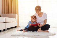 Leitura chinesa asiática da mãe e da filha no assoalho fotos de stock royalty free